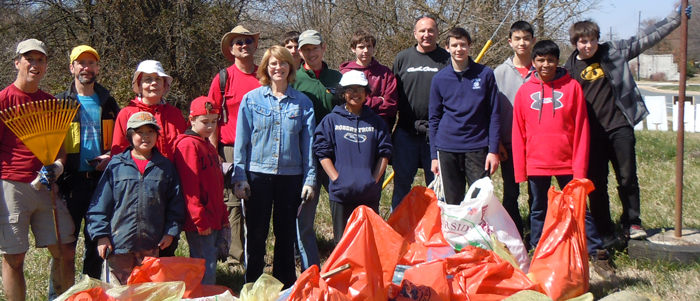 Adults and children clean up community streams