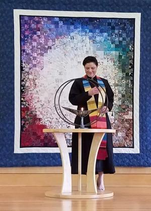 Rev. Rebekah A. Savage at UUCR's chalice before displayed quilt.